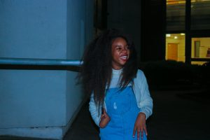 Rachy wearing white sweater with denim overalls. She is smiling.