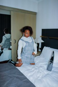 Rachy kneeling on a bed next to check print handbag