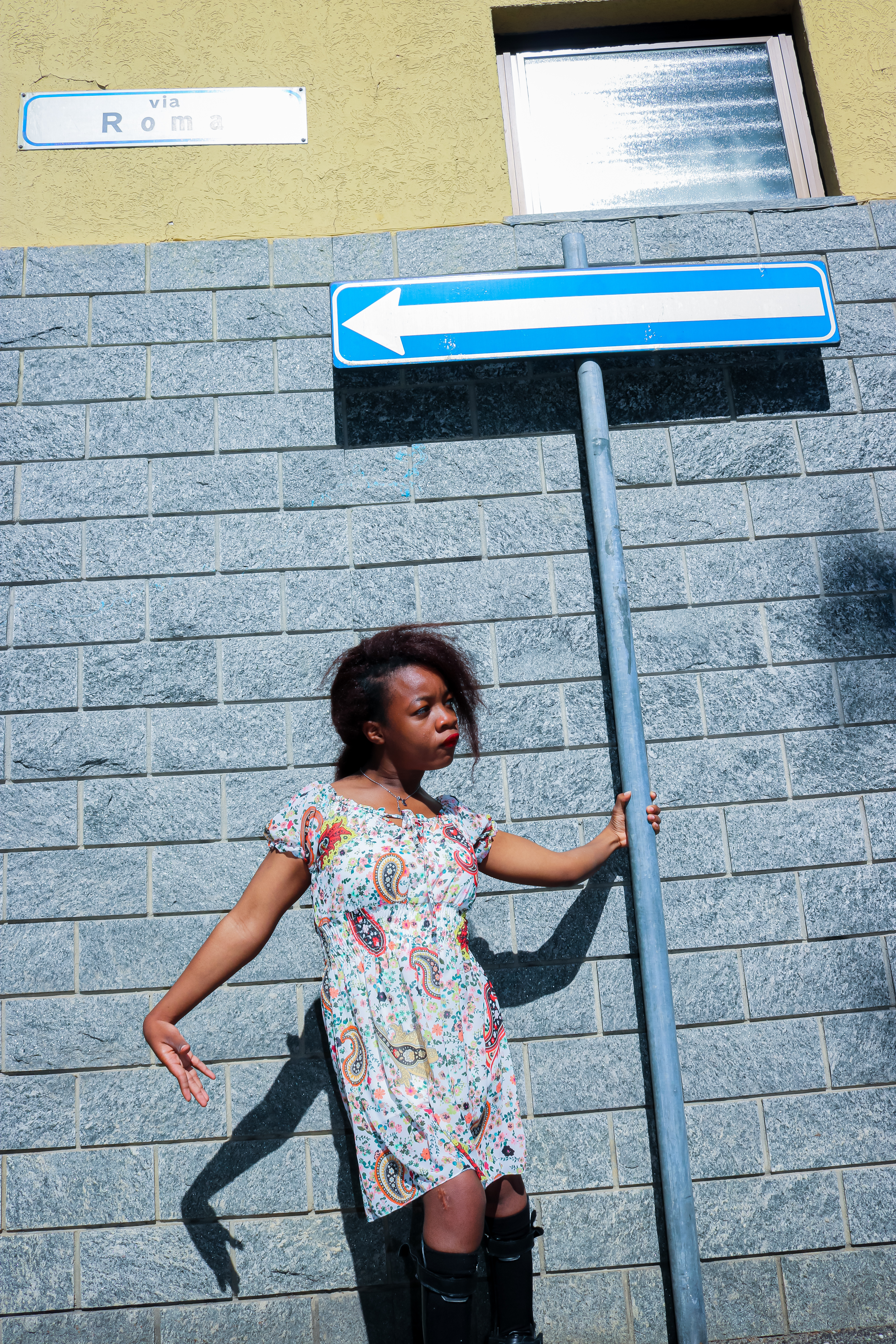 Rachy standing in front of a road sign with an arrow pointed left