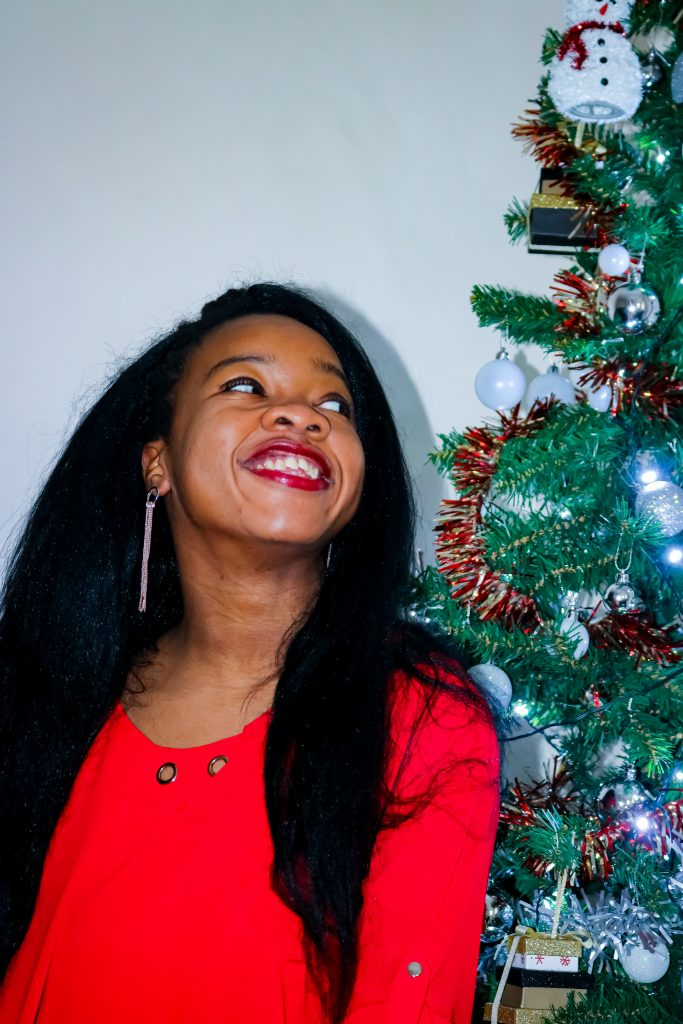 rachy sat by christmas tree smiling