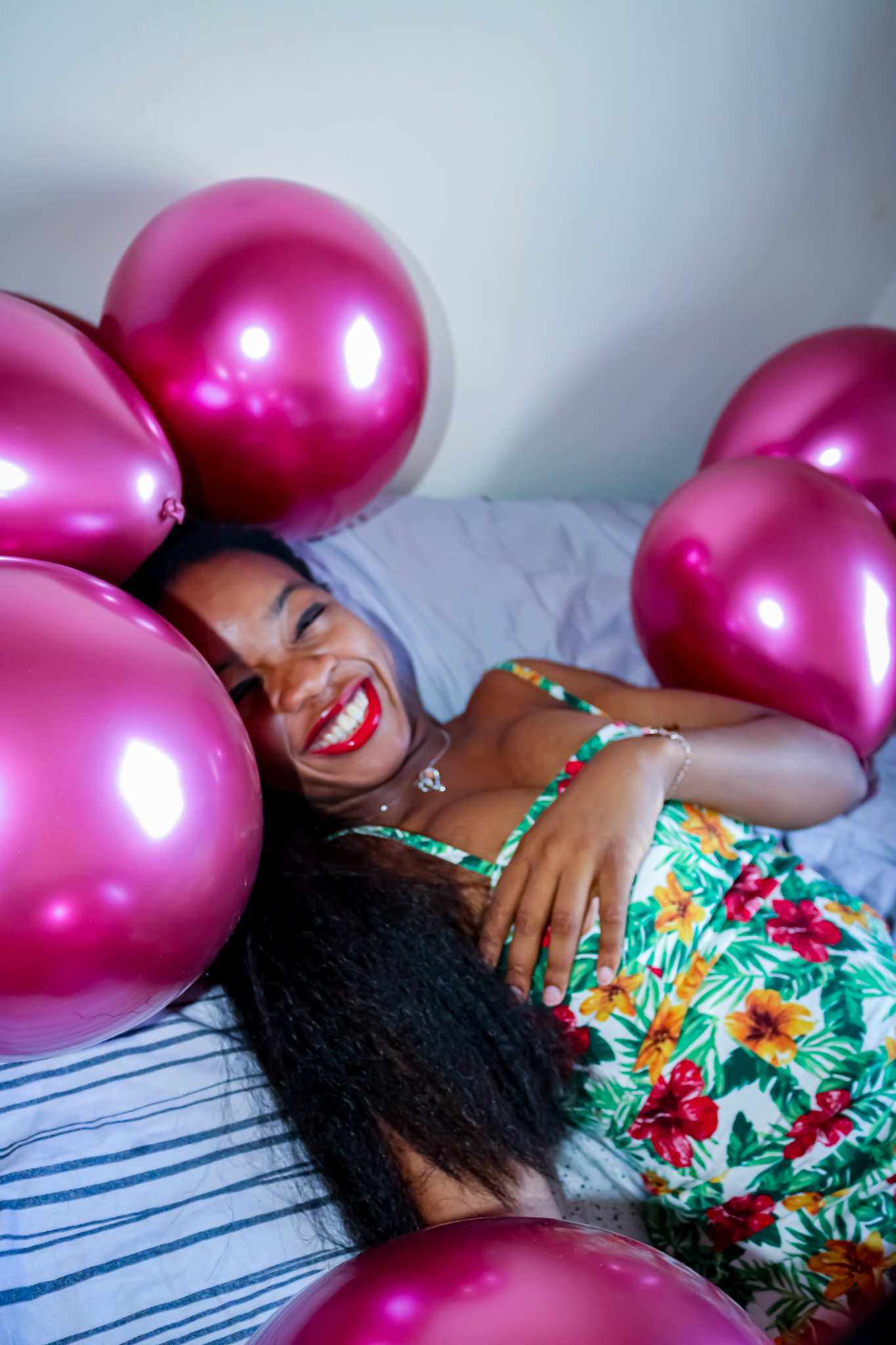 Rachy Lewis smiling in floral dress surrounded by balloons